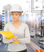 Female contractor in helmet with folder — Stock Photo