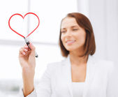 Businesswoman drawing heart in the air — Stock Photo