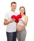 Gelukkig jonge familie verwachten kind met groot hart — Stockfoto