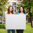 Two smiling young girls with blank white board — Stock Photo