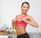 Sporty woman measuring her breast — Stock Photo