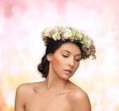 Beautiful woman wearing wreath of flowers — Stockfoto