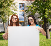 Two smiling girls with eyeglasses and blank board — Stock Photo