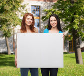 Two smiling young girls with blank white board — Stok fotoğraf
