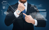 Businessman pointing to something at his hand — Stock Photo