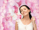 Beautiful woman spraying pefrume on her neck — Stock Photo