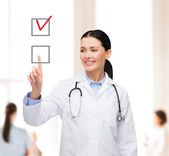Smiling female doctor pointing checkbox — Foto Stock