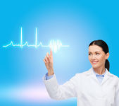 Smiling female doctor pointing to cardiogram — Stock Photo