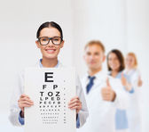 Female doctor in eyeglasses with eye chart — Stock Photo