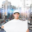 Male architect in helmet with blueprint — Stock Photo #39392369