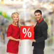 Smiling man and woman with percent sign — Stock Photo #39392519