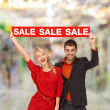 Smiling woman and man with red sale sign — Stock Photo #39392579