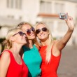 Stock Photo: Three beautiful girls taking picture in city