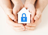Hands holding paper house with lock — Stock Photo