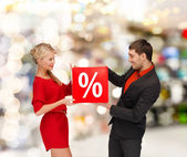 Smiling woman and man with red percent sale sign — Stock Photo