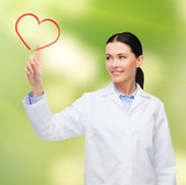Smiling female doctor pointing to heart — Stock Photo