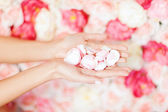 Womans cupped hands with flower petals — Stockfoto