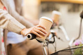 Woman hand holding coffee and riding bicycle — Stock Photo