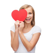 Smiling woman in white t-shirt with heart — Stockfoto
