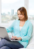 Happy woman with laptop at home — Stockfoto