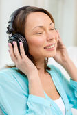 Smiling woman with headphones at home — Stock Photo