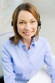 Female helpline operator with headphones — Stock Photo