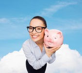 Happy businesswoman in eyeglasses with piggy bank — Stock Photo