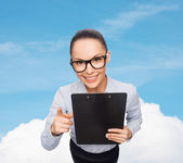 Smiling businesswoman in eyeglasses with clipboard — Stockfoto