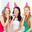 Three smiling women in hats blowing favor horns — Stockfoto #39653957
