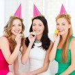 Three smiling women in hats blowing favor horns — Stock Photo #39653957