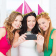 Three smiling women in hats having fun with camera — Stockfoto #39653983
