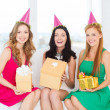 Three smiling women in pink hats with gift boxes — Stock Photo