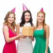 Three smiling women in blue hats with gift box — Stock Photo #39654039