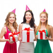 Three smiling women in blue hats with gift boxes — Stock fotografie #39654041