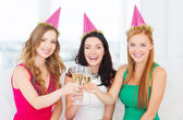 Three women wearing hats with champagne glasses — 图库照片