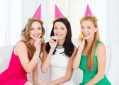 Three smiling women in hats blowing favor horns — Стоковое фото