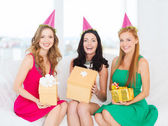 Three smiling women in pink hats with gift boxes — Stok fotoğraf