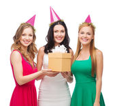 Three smiling women in blue hats with gift box — Stok fotoğraf