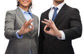 Businessman and businesswoman showing ok sign — Stockfoto