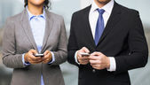 Businessman and businesswoman with smartphones — Stock Photo