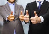 Businessman and businesswoman showing thumbs up — Stock Photo