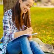 Smiling teenager writing in notebook — Stock Photo