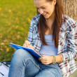 Smiling teenager writing in notebook — Stock Photo #39661081
