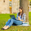 Teenager in eyeglasses with laptop and coffee — Stockfoto