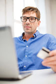 Man with laptop and credit card at home — Stock Photo