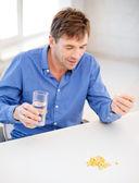 Chory człowiek biorąc jego pigułki w domu — Zdjęcie stockowe