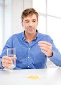 Człowiek w domu pokazano wiele tabletek — Zdjęcie stockowe