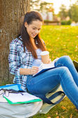 Teenager reading book with take away coffee — Stock Photo
