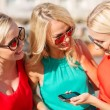 Beautiful girls with smartphone in the city — Stock Photo