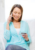 Mujer sonriente con el smartphone en casa — Foto de Stock